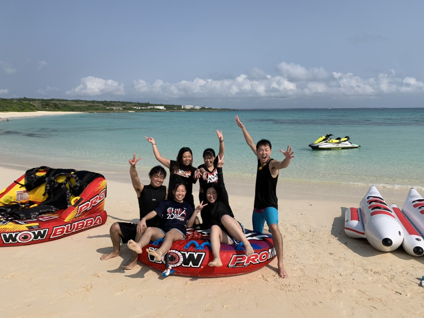 バナナボートに乗ってポーズを決める若い男女5人グループ