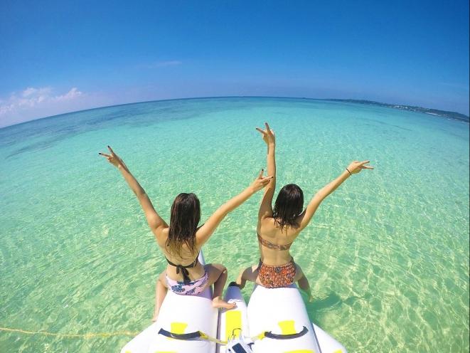 海に向かってバンザイする女性2人