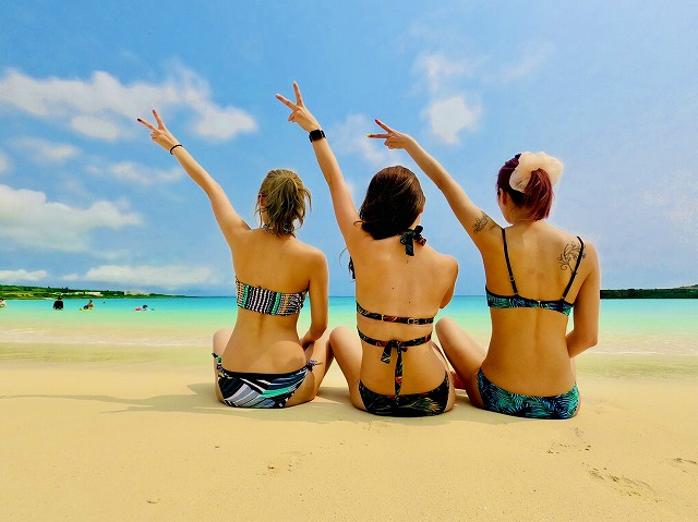 渡口の浜ビーチに座る3人組女性の後ろ姿