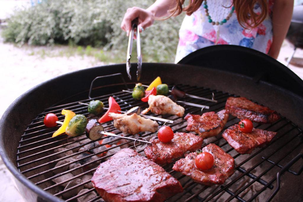 バーベキューで肉を焼く女性